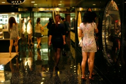 Prostitutes from mainland China wait for customers inside the shopping mall of a hotel in Macau December 18, 2009, two days before the 10th anniversary of its handover to China. As Macau marks its first decade under Chinese rule on Sunday, the quiet Portuguese enclave turned gaming hub remains beset by a tangle of challenges that could yet tarnish its future economic prospects and impact on governance.   REUTERS/Bobby Yip  (CHINA - Tags: POLITICS BUSINESS ANNIVERSARY)