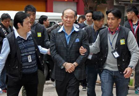 """This handout picture released by Apple Daily on January 13, 2015 shows Alan Ho (C) being led away by police officers on January 12, 2015 after his arrest. Chinese gambling enclave Macau has busted a major prostitution ring comprising nearly 100 sex workers and arrested the nephew of gaming tycoon Stanley Ho, who is involved with the ring, city authorities said.  CHINA OUT HONG KONG OUT TAIWAN OUT     AFP PHOTO / APPLE DAILY - EDITORS NOTE - RESTRICTED TO EDITORIAL USE - MANDATORY CREDIT """"AFP PHOTO / APPLE DAILY"""" - NO MARKETING - NO ADVERTISING CAMPAIGNS - NO INTERNET - DISTRIBUTED AS A SERVICE TO CLIENTS - NO ARCHIVES"""
