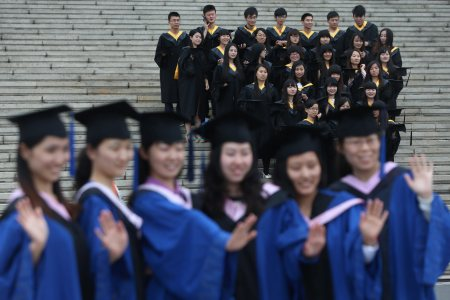 epa04246356 Chinese college graduates pose for their group graduation photograph at the Qingdao University, Shandong province, eastern China, 09 June 2014. The number of Chinese college graduates hit a historical high record reaching 7.27 million in 2014, increased by 280,000 compared to previous year, according to official figures.  EPA/WU HONG