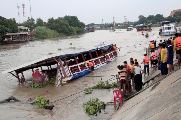People stand near a boat which according to officials, capsized on the Chao Phraya river while carrying 150 Thai Muslims, in the ancient tourist city of Ayutthaya
