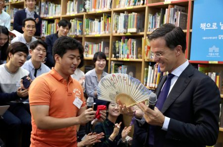epa05559630 A picture made available on 28 September 2016 shows visiting Dutch Prime Minister Mark Rutte (R) receiving a traditional folding fan from a student during a meeting with South Korean students at the library in Seoul City Hall, South Korea, 27 September 2016.  EPA/YONHAP SOUTH KOREA OUT