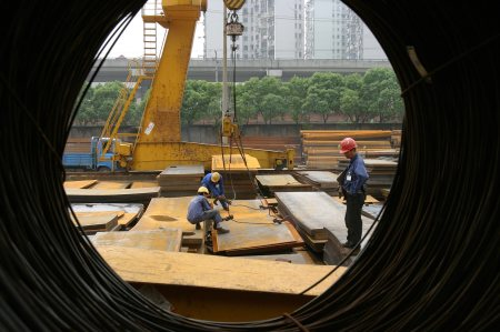 Workers attach crane cables to steel plates at a trading stockyard in Shanghai, China
