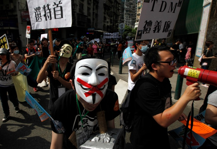 Pro-democracy demonstrators hold placards during a protest march in Macau