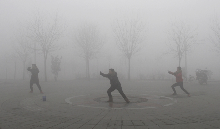 People practise Taiji on a foggy day at a park in Jiaozuo