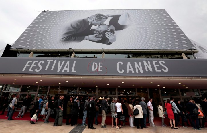 Visitors wait to enter in the Festival Palace covered by a giant canvas of the official poster of the 66th Cannes Film Festival in Cannes