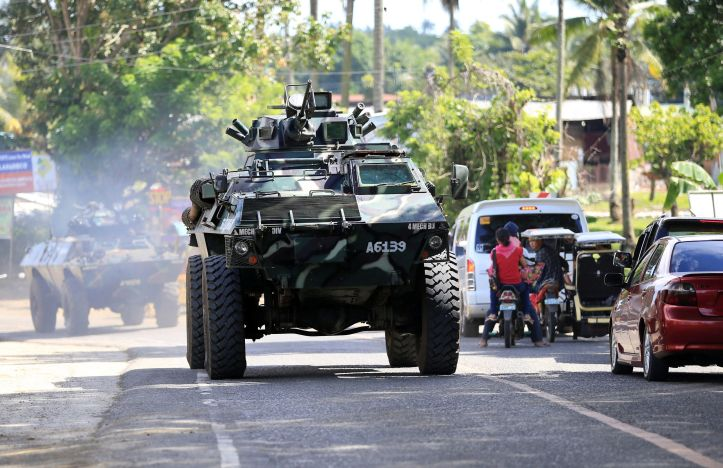 126649093_an-armoured-personnel-carrier-belonging-to-government-troops-drives-along-a-main-highway-o.jpg